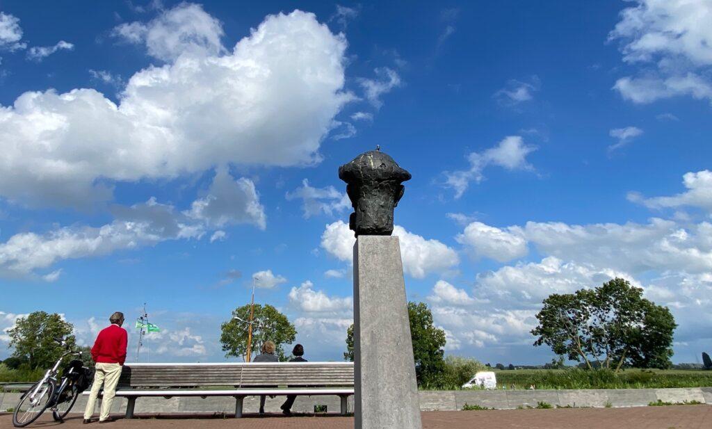 Voerman buste met uitzicht op de wolkenluchten boven de IJssel